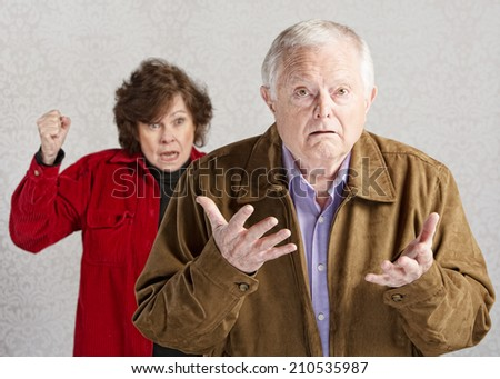 Confused elderly man with angry older woman - stock photo