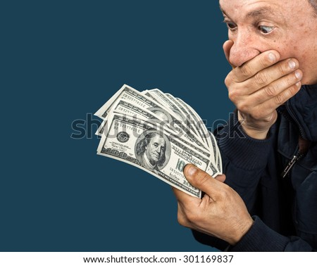 Confused elderly man with fan of dollars on dark blue background with copy-space - stock photo