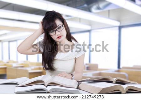 Confused female student reading many books for exam in the library - stock photo