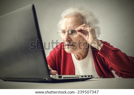 Confused grandmother using a pc  - stock photo