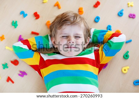 Confused little kid boy playing with lots of colorful plastic digits or numbers, indoor. child wearing colorful shirt and having fun with learning math - stock photo
