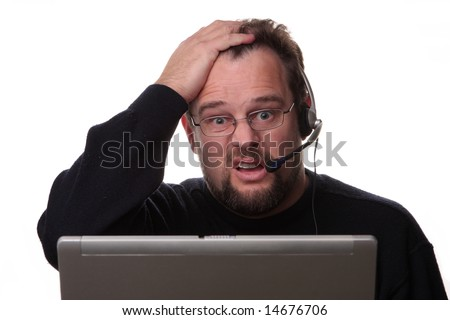 Confused looking 30-something computer operator on white background wearing phone headset - stock photo