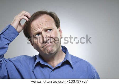 Confused Mid-Adult Man Scratching His Head - stock photo