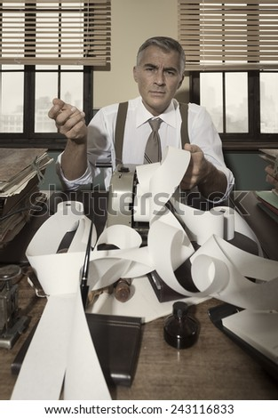 Confused pensive accountant checking very long bills on cash register tape, 1950s style office. - stock photo