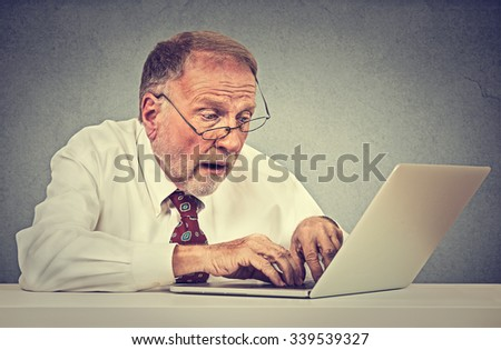 Confused surprised senior man using a pc laptop computer   - stock photo