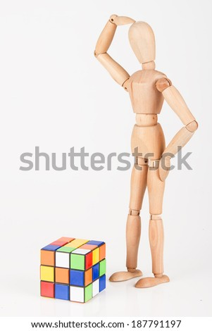 Confused wood mannequin stand next to puzzle confused before attempt to solve it - stock photo