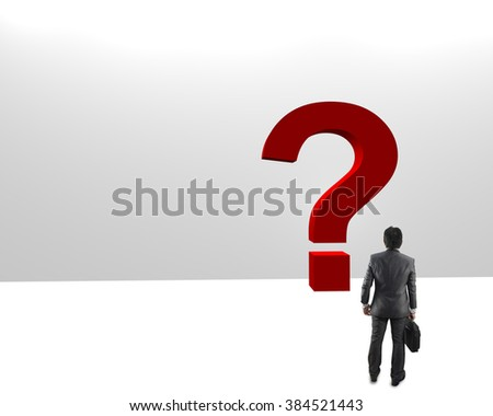 Confused, young businessman looking at red question marks - stock photo