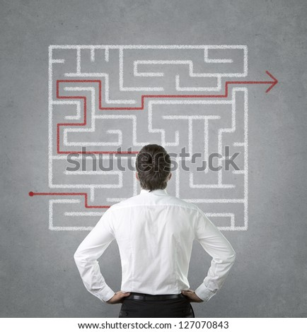 Confused, young businessman looking at the red arrow through the labyrinth - stock photo