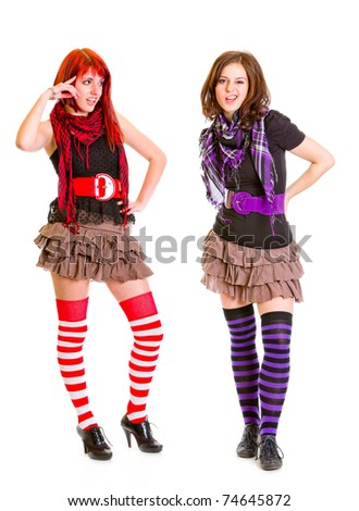 Confused young girl looking on her grimacing girlfriend isolated on white - stock photo