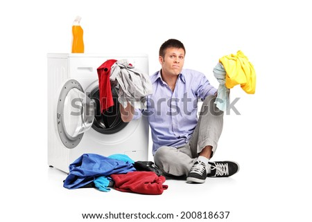 Confused young man doing laundry seated by a washing machine isolated on white background - stock photo