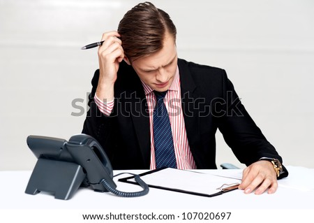 Confused young man itching his head with pen. Sitting at work desk - stock photo