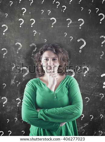 Confused young woman and question marks on the blackboard behind her.  - stock photo