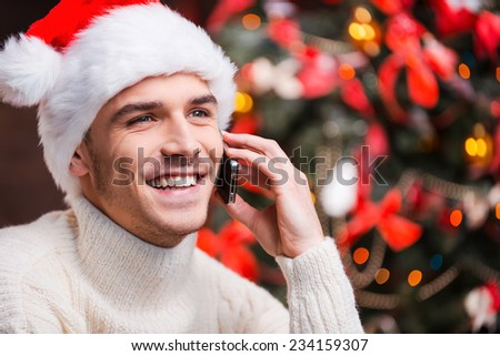 Congratulating his nearest. Handsome young man in Santa hat talking on mobile phone and smiling with Christmas Tree in the background  - stock photo