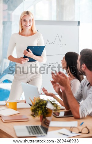 Congratulating with success. Beautiful young woman standing near whiteboard and smiling while her colleagues sitting at the desk and applauding - stock photo