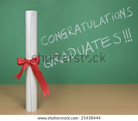 Congratulations graduates written on a chalkboard with a diploma on forefround. - stock photo