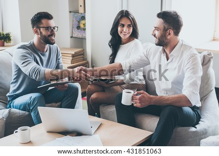 Congratulations! Three young cheerful business people sitting together at the desk while men shaking hands  - stock photo