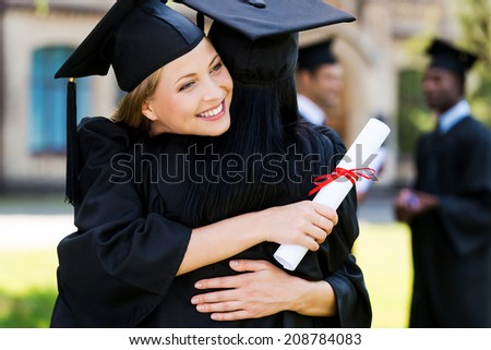 Congratulations! Two happy woman in graduation gowns hugging and smiling while two men standing in the background  - stock photo