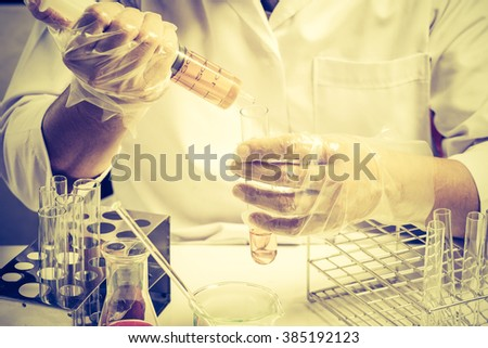 Conical flask in scientist hand with lab glassware background, Laboratory research concept.vintage porcess style - stock photo