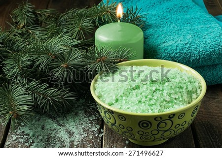 Conifer spa products: sea salt with pine oil, scented candles, pine branch, a towel on the wooden background - stock photo