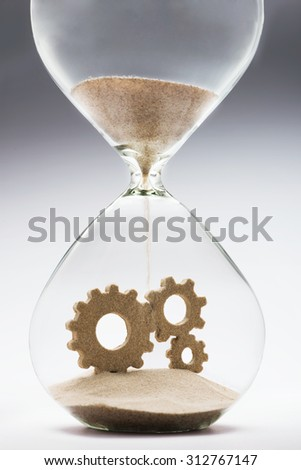 Connected gears made out of falling sand inside hourglass - stock photo