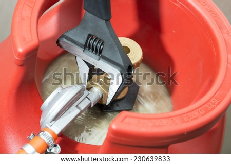 Connecting hose with damper to a gas cylinder , by the adjustable wrench. - stock photo