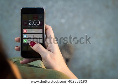 connectivity concept: Top view of woman walking in the street using her mobile phone with notifications on screen. All screen graphics are made up. - stock photo