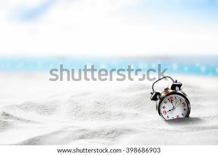 Connotation of Alarm clock sink to sand on beach side with sunny day blue sky. - stock photo