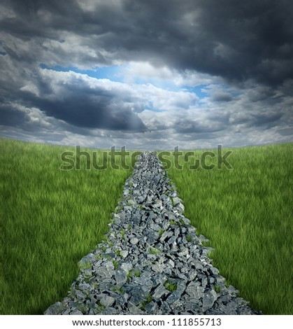 Conquering adversity and overcoming business challenges with a bumpy highway path made of rough rocks into a perspective horizon with storm clouds and a glimmer of sun shinning through the dark sky. - stock photo