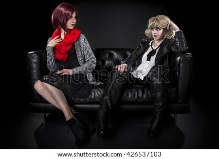 Conservative female model snobbish to a younger model in goth punk fashion clothing - stock photo
