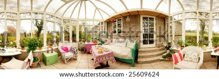 conservatory interior with sofa and chairs. panoramic image of glass extension - stock photo