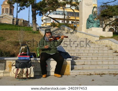 CONSTANTA,ROMANIA - DECEMBER 12, 2014. Beautiful winter day on the waterfront at the Black Sea in Constanta City ,Romania . Man playing the violin and enchant  visitors. - stock photo