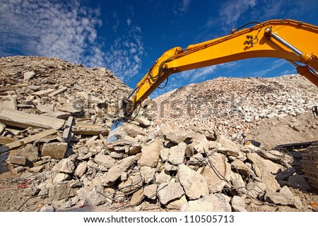 Construction and concrete demolition waste recycling site with excavator boom crusher - stock photo