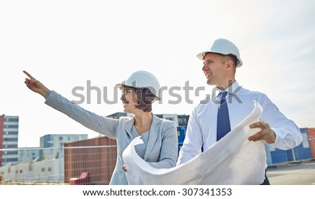 construction, architecture, business, teamwork and people concept - happy architects with blueprint at building site - stock photo