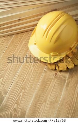 Construction background. Yellow helmet on wooden floor. - stock photo