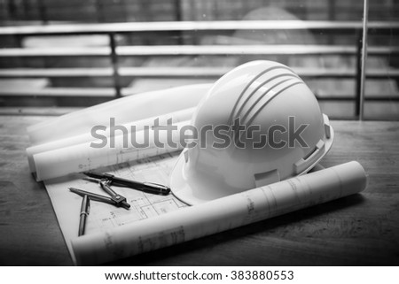 construction concept image helmet rolled blueprints on wooden boards in retro style. - stock photo
