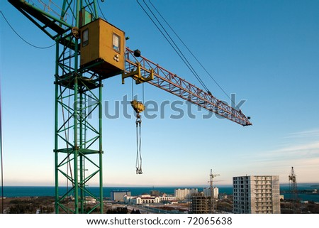 Construction crane against the blue sky and the houses under construction - stock photo