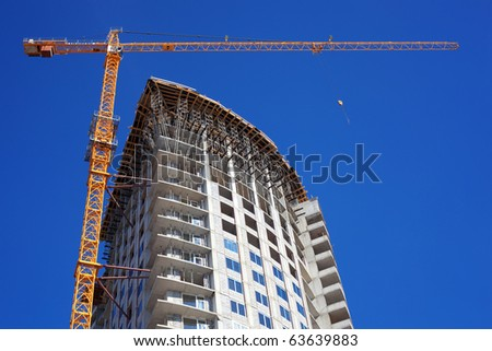 Construction crane against the blue sky building under construction - stock photo