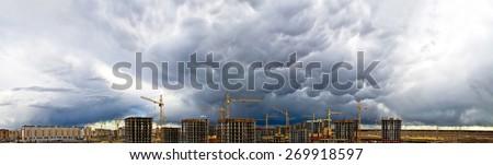 Construction crane industrial concrete skyscraper storm rain weather sky panorama - stock photo