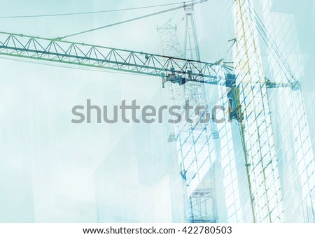 Construction cranes on a background of abstract buildings - stock photo