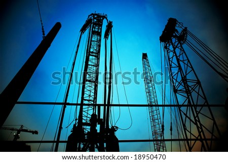 construction cranes on night over a blue sky - stock photo
