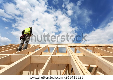 Construction crew working on the roof against blue sky - stock photo
