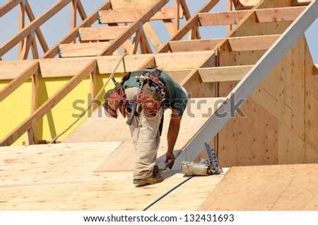 Construction crew working on the roof sheeting of a new, two story, commercial apartment building in Oregon - stock photo