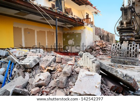 Construction/demolition pile of rubble with partially demolished house in background. Focus on foreground debris. - stock photo