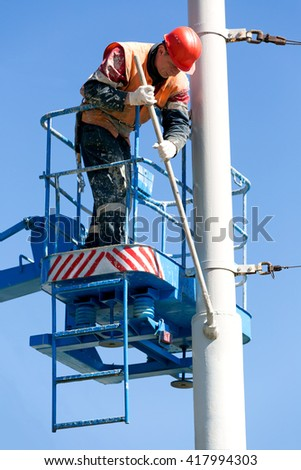 Construction dirty Painter Worker Man with Hard Hat Helmet and Safety Protective Equipment Painting street pole at Height with Brush Tool - stock photo
