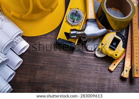 Construction drawings and set of building objects on vintage pine wooden board maintenance concept  - stock photo
