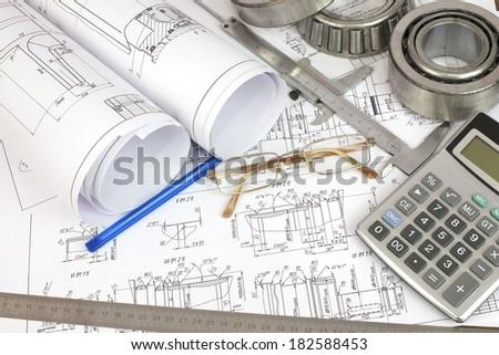 Construction drawings, caliper, bearing, calculator, pen, ruler and glasses. Desk Engineer - stock photo