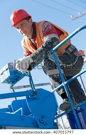 Construction Electrician Worker Man in dirty  workwear with Hard Hat helmet and Safety Protective Equipment during work at Height - stock photo