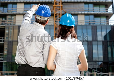 Construction engineer pointing on an area of the building on construction site - stock photo