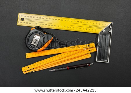 Construction engineer's tools: right angle, measuring tape, measuring ruler and pencil - stock photo