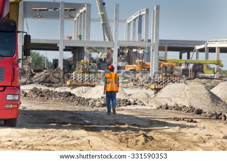 Construction engineer supervising work at building site - stock photo